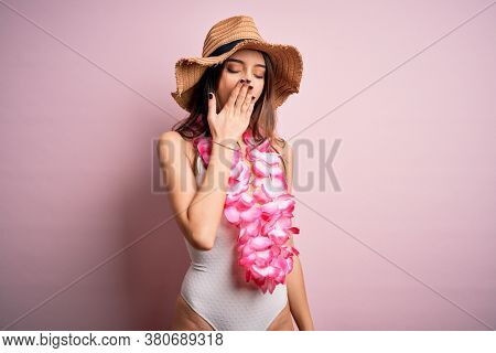 Young beautiful brunette woman on vacation wearing swimsuit and Hawaiian flowers lei bored yawning tired covering mouth with hand. Restless and sleepiness.