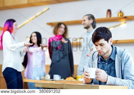 Closeup Portrait Of Sad Man, Outcast Is Sitting Alone At Table In Cafe. Teenagers, Students Are Mock