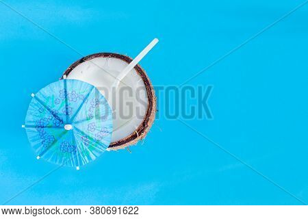 Brown Half Of Coconut Nut With White Milk And Straw Inside On Blue Background. Tropical Exotic Fruit