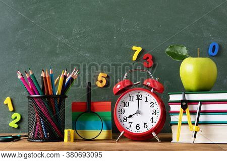 Back To School Or Education Concept With Alarm Clock, School Supplies And Fresh Green Apple Against