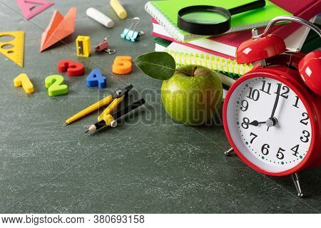 Starting Education Or Back To School Concept With Red Alarm Clock, Fresh Green Apple And Colorful Sc