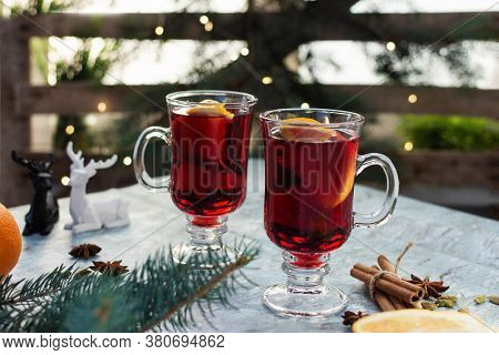 Christmas Mulled Red Wine With Spices And Fruits Over Christmas Decorated Background.