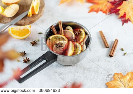 Hot Mulled Wine With Citrus, Apples, Cinnamon Sticks, And Anise Stars In Cooking Pan On Grey Table B