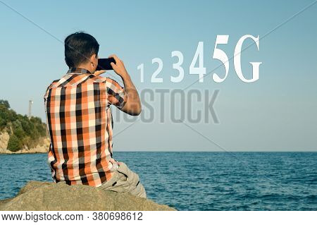 A Young Man With A Mobile Phone Takes Photos And Videos Of A Travel To Share On Social Networks Usin