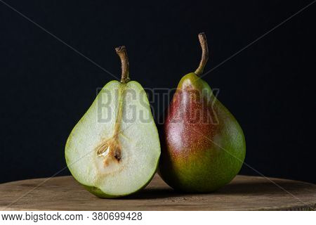 Pears On A Black Background. One Pear Is Whole, The Other Is Cut In Half. Fresh Juicy Pears