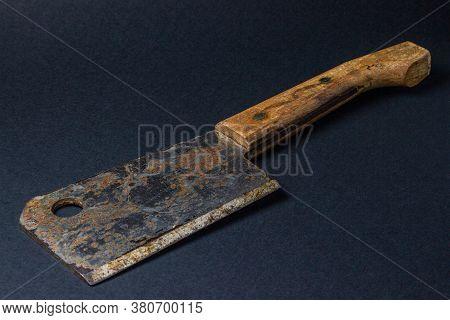 Hatchet On A Black Background. Old Rusty Kitchen Hatchet. Household Item. Kitchenware