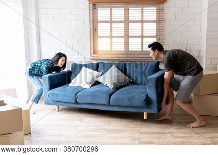 An Asian Couple, Husband And Attractive Wife, Are Helping To Lift For Moving The Sofa In Their New H