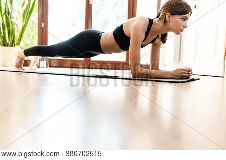 Attractive young woman working out at home, doing yoga exercise on blue mat, plank exercise