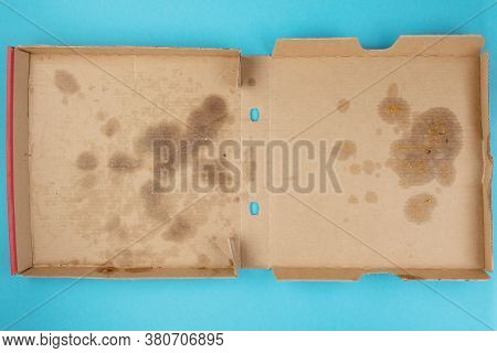 Above View Of Greasy Empty Delivery Pizza Box On Blue Background