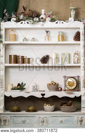 Stylish Antique Decor With Pine Cones. White Cabinet With Antiques On The Shelves.