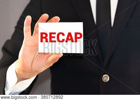 Recap Word On White Card Paper Sheet On In Hands Of A Businessman Blurred. Recap Concept.