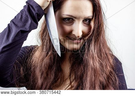 Young Caucasian Insane Brunette Woman With Knife In Black Against Light Background. Halloween Concep