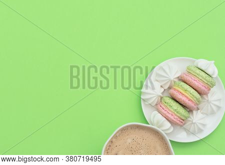 The Cup Of Cappuccino And Delicious Macarons With White Merengues On White Plate On Green Background
