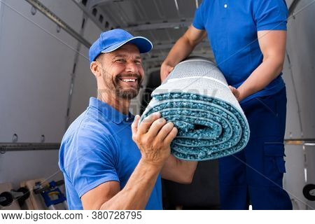 Movers Moving Carpet From Truck Or Van
