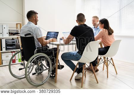 Disabled People In Wheelchair At Workplace Business Meeting