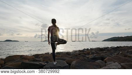 Woman do yoga and sit at seaside