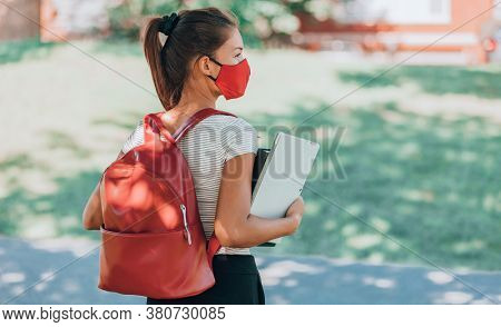 Back to school concept. University student wearing mask walking on campus with backpack, books and laptop.