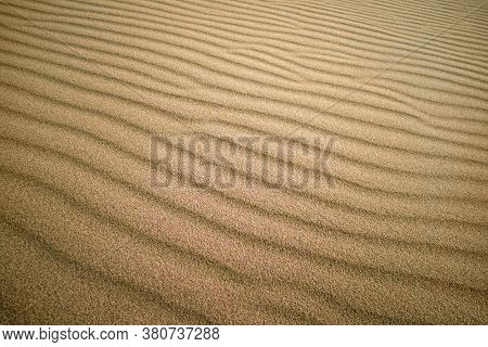 Sand Texture Background And Sand Dunes - Image. Yellow Sand Dune In The Sun. The Sun Shines On The S