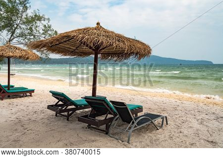 Beach Calm Scene With Sunbeds And Straw Umbrellas Under Coconut Palms Close To Caribbean Sea. Tropic