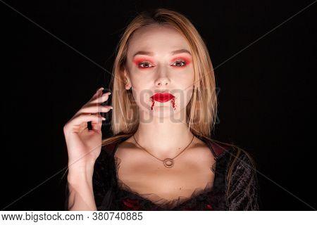 Portrait Of Beautiful Vampire Woman Over Black Background. Attractive Vampire.