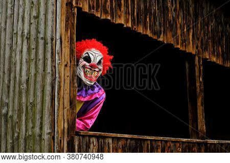 Halloween Holiday. Creepy Clown Costume. Spooky Clown In A Bright Overalls In An Old Wooden Hut.autu
