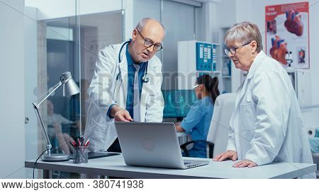 Elderly Experienced Doctors Consulting Each Other In Modern Private Clinic With Glass Walls. Senior