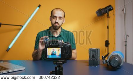 Photographer Talking About Lens Specification While Recording Vlog Episode For Subscribers. Camera L