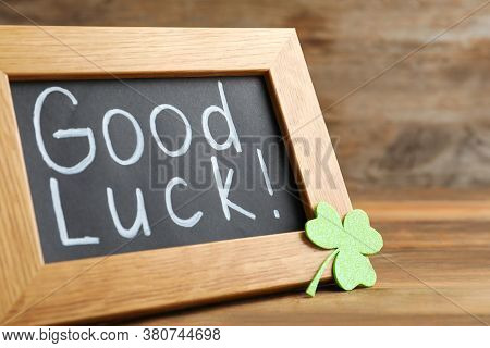 Blackboard With Phrase Good Luck And Clover Leaf On Wooden Table, Closeup