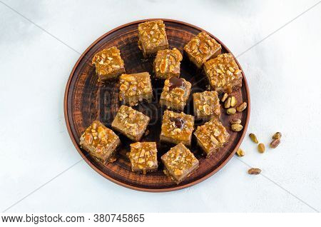Chocolate Fudge Bars With Nuts On A Brown Plate On A White Background. Clean Eating Concept. Raw Veg