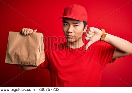 Young handsome chinese delivery man holding takeaway paper bag with food with angry face, negative sign showing dislike with thumbs down, rejection concept