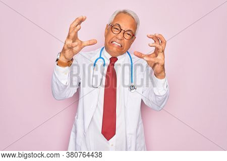 Middle age senior grey-haired doctor man wearing stethoscope and professional medical coat Shouting frustrated with rage, hands trying to strangle, yelling mad