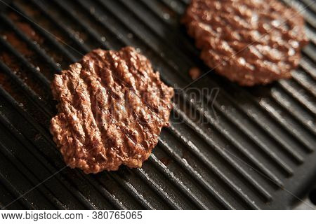 Beef Burger Patties On Griddle Pan Cooking. Copy Space For Design Mockup
