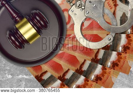 50 Canadian Dollars Bills And Judge Hammer With Police Handcuffs On Court Desk. Concept Of Judicial