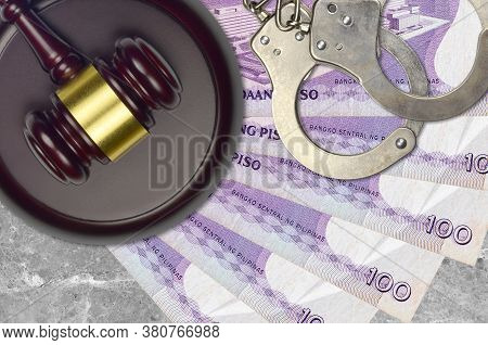 100 Philippine Piso Bills And Judge Hammer With Police Handcuffs On Court Desk. Concept Of Judicial