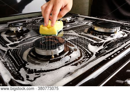 Washing The Surface On A Gas Stove, Cleaning The Surface With A Yellow Washcloth, White Foam.