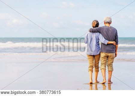 Asian couple senior walking on the beach holding hands.Honeymoon family together happiness lifestyle.Life after retirement.plan life insurance