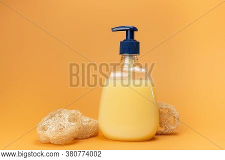 A Bottle Of Yellow Liquid Soap And A Washcloth Made Of Natural Material - The Root Of The Plant On A