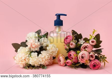 Yellow Liquid Soap Bottle And Beautiful Delicate Flowers On A Pink Background. Clean Hands Concept.