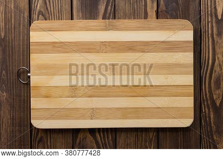 A Wooden Cutting Board With A Striped Surface In Dark And Light Wood And A Ring On A Wooden Table. U