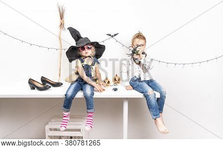 A Little Boy In A Zombie Costume And A Girl In A Witch Costume Are Sitting On The Table.