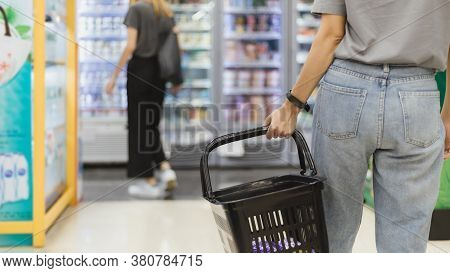 Closeup Of Woman's Hand Holding Empty Market Basket Doing Shopping At Supermarket Or Grocery With. S
