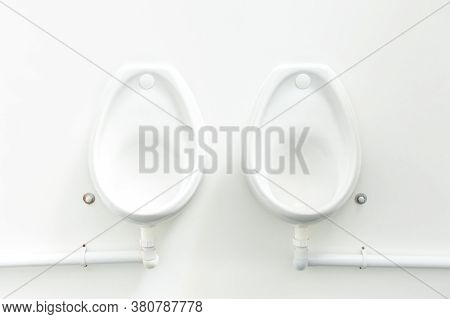Clean White Public Urinals Fixed To A White Wall