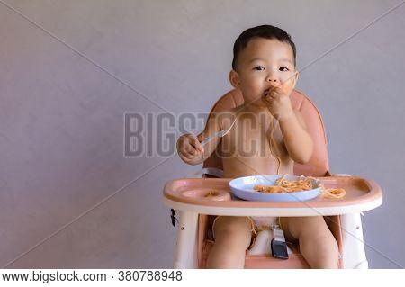 Asian Boy Eatting On High Baby Chair.