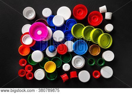 Composition Of Plastic Bottle Caps. Top View Of Recycled Plastic Bottle Caps. Separate Garbage Colle