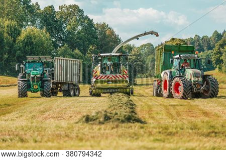 Bavaria / Germany - August 07,2020: Claas Jaguar 930 Harvester, A John Deere 6175r Tractor And A Fen