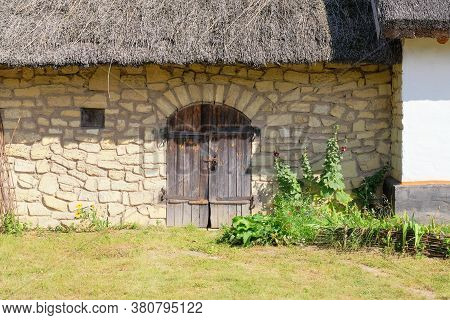 Old Rural House With Thatched Roof. Village Is Preserving Rustic Traditions And Culture.