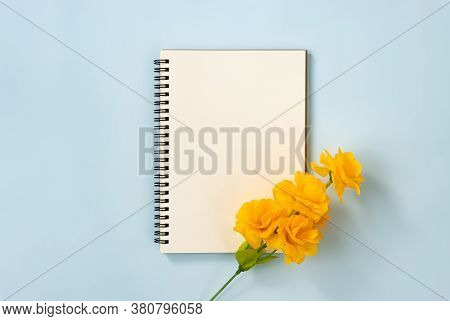 Spiral Notebook Or Spring Notebook In Unlined Type And Orange Yellow Flowers At Bottom Right On Blue
