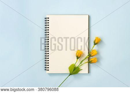 Spiral Notebook Or Spring Notebook In Unlined Type And 4 Orange Flowers At Bottom Right On Blue Past