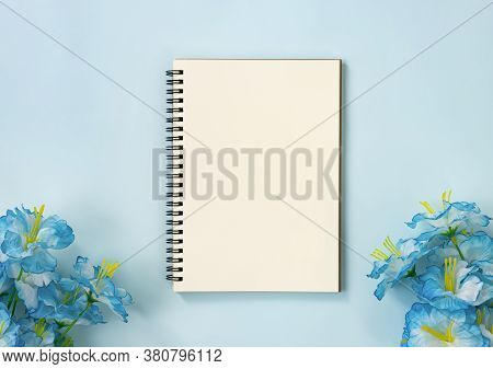 Spiral Notebook Or Spring Notebook In Unlined Type And Blue Flowers At Bottom On Blue Pastel Minimal