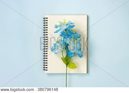 Spiral Notebook Or Spring Notebook In Unlined Type And Blue Flowers At Center On Blue Pastel Minimal
